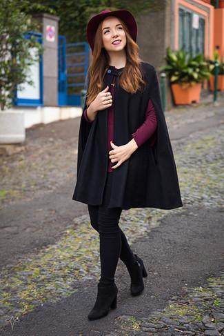 Wie kombinieren: schwarzer Cape Mantel, dunkelrote Langarmbluse, schwarze enge Jeans, schwarze Wildleder Stiefeletten