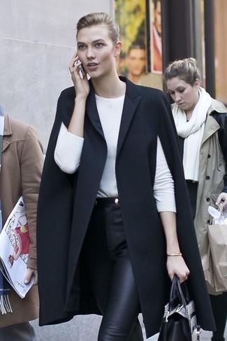 Wie kombinieren: schwarzer Cape Mantel, weißes Langarmshirt, schwarze enge Hose aus Leder, graue Shopper Tasche aus Leder mit Schlangenmuster