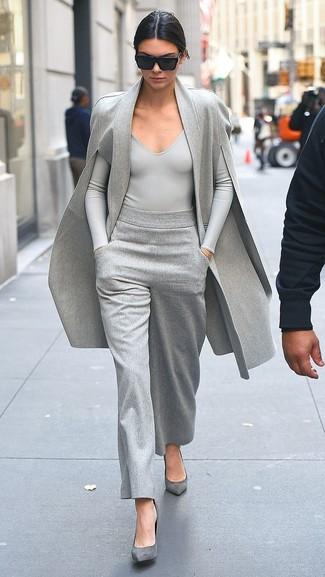 Damen Outfits 2020: Wer perfekt aber locker gekleidet sein will, setzt oft auf modische Outfits, wie zum Beispiel die Paarung aus einem grauen Cape Mantel und einer grauen weiter Hose. Graue Wildleder Pumps sind eine ideale Wahl, um dieses Outfit zu vervollständigen.
