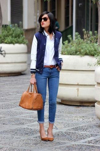 Wie kombinieren: dunkelblaue und weiße Collegejacke, weißes Businesshemd, blaue enge Jeans, braune Wildleder Pumps