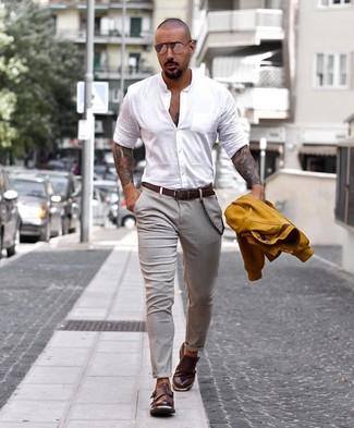 Wie kombinieren: senf Collegejacke, weißes Langarmhemd, graue Chinohose, dunkelbraune Doppelmonks aus Leder