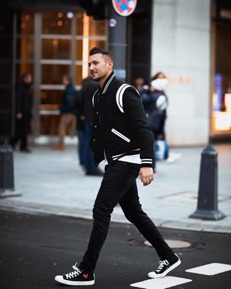 Wie kombinieren: schwarze und weiße Collegejacke, weißes T-Shirt mit einem Rundhalsausschnitt, schwarze enge Jeans, schwarze und weiße Segeltuch niedrige Sneakers