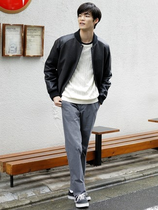 Wie kombinieren: schwarze Collegejacke, weißer Strickpullover, schwarzes T-Shirt mit einem Rundhalsausschnitt, graue Chinohose