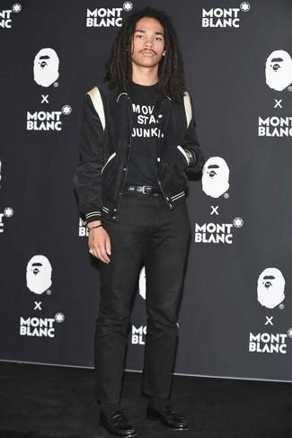 Wie kombinieren: schwarze und weiße Collegejacke, schwarzes und weißes bedrucktes T-Shirt mit einem Rundhalsausschnitt, schwarze Chinohose, schwarze Leder Slipper