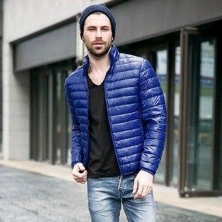 Wie kombinieren: blaue Daunenjacke, schwarzes T-Shirt mit einem V-Ausschnitt, blaue Jeans, dunkelblaue Mütze