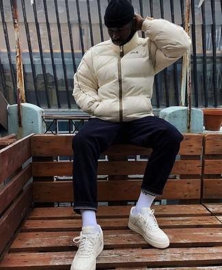 Wie kombinieren: hellbeige Daunenjacke, dunkelblaue Jeans, hellbeige Leder niedrige Sneakers, schwarze Mütze