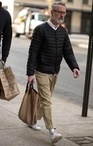 Herren Outfits & Modetrends 2020: Entscheiden Sie sich für eine schwarze Daunenjacke und eine beige Chinohose, um einen eleganten, aber nicht zu festlichen Look zu kreieren. Suchen Sie nach leichtem Schuhwerk? Komplettieren Sie Ihr Outfit mit weißen Leder niedrigen Sneakers für den Tag.
