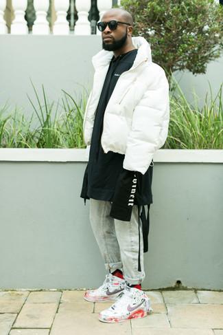 Wie kombinieren: weiße Daunenjacke, schwarzer und weißer bedruckter Pullover mit einem Kapuze, hellblaue Jeans, weiße bedruckte hohe Sneakers aus Leder