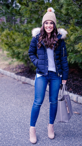 Wie kombinieren: dunkelblaue Daunenjacke, grauer Pullover mit einem Rundhalsausschnitt, blaue enge Jeans mit Destroyed-Effekten, hellbeige Wildleder Stiefeletten