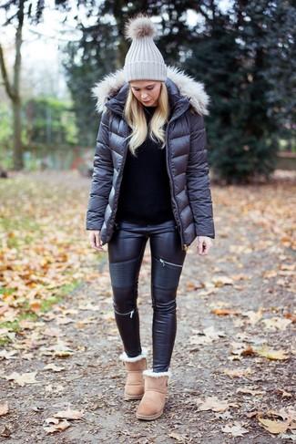 Wie kombinieren: dunkelgraue Daunenjacke, schwarzer Pullover mit einem Rundhalsausschnitt, schwarze Leder enge Jeans, hellbeige Ugg Stiefel