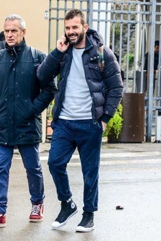 Grauen Pullover mit einem Rundhalsausschnitt kombinieren: trends 2020: Entscheiden Sie sich für einen grauen Pullover mit einem Rundhalsausschnitt und dunkelblauen Jeans für ein sonntägliches Mittagessen mit Freunden. Wählen Sie die legere Option mit schwarzen hohen Sneakers aus Segeltuch.