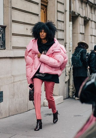 Wie kombinieren: rosa Daunenjacke, schwarzer bedruckter Pullover mit einer Kapuze, rosa Anzughose, schwarze bedruckte Leder Stiefeletten
