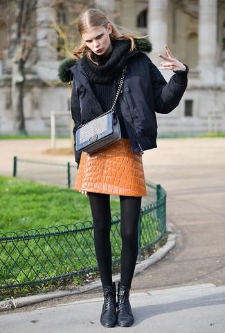 Wie kombinieren: schwarze Daunenjacke, schwarzer Pullover mit einer weiten Rollkragen, orange Leder Minirock, schwarze flache Stiefel mit einer Schnürung aus Leder