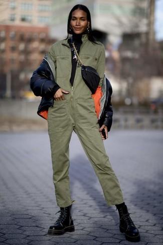 Wie kombinieren: schwarze Daunenjacke, schwarzer Rollkragenpullover, olivgrüner Jumpsuit, schwarze flache Stiefel mit einer Schnürung aus Leder
