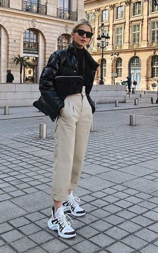 Wie kombinieren: schwarze Daunenjacke, schwarzer Rollkragenpullover, hellbeige Karottenhose, weiße und schwarze Sportschuhe