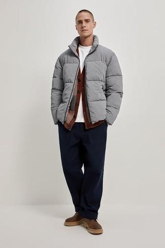 Herren Outfits 2020: Etwas Einfaches wie die Paarung aus einer grauen Daunenjacke und einer dunkelblauen Chinohose kann Sie von der Menge abheben. Braune Chukka-Stiefel aus Leder sind eine perfekte Wahl, um dieses Outfit zu vervollständigen.