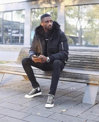 Wie kombinieren: schwarze Daunenjacke, schwarzes Sweatshirt, schwarze enge Jeans, schwarze und weiße hohe Sneakers aus Segeltuch
