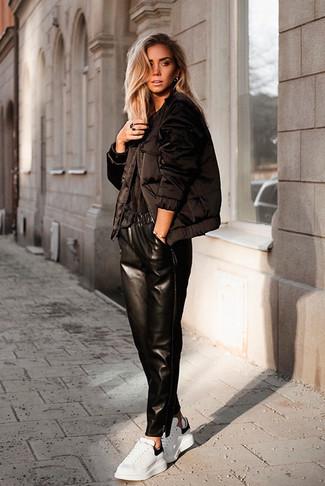Wie kombinieren: schwarze Daunenjacke, schwarzes T-Shirt mit einem Rundhalsausschnitt, schwarze Freizeithose aus Leder, weiße Leder niedrige Sneakers