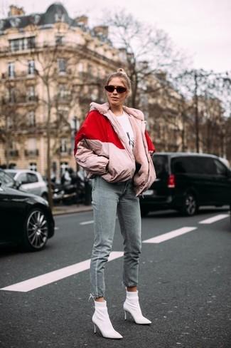 Wie kombinieren: rosa Daunenjacke, weißes und schwarzes bedrucktes T-Shirt mit einem Rundhalsausschnitt, graue Jeans, weiße elastische Stiefeletten