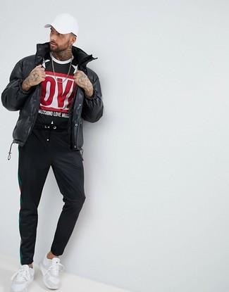 Wie kombinieren: schwarze Daunenjacke, schwarzes bedrucktes T-Shirt mit einem Rundhalsausschnitt, schwarze Jogginghose, weiße Sportschuhe