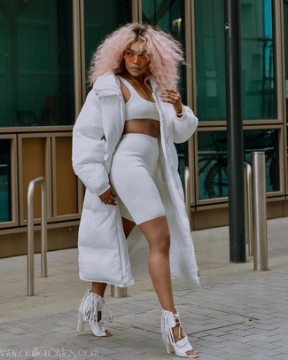 Wie kombinieren: weißer Daunenmantel, weißes kurzes Oberteil, weiße Radlerhose, weiße Leder Sandaletten mit Fransen