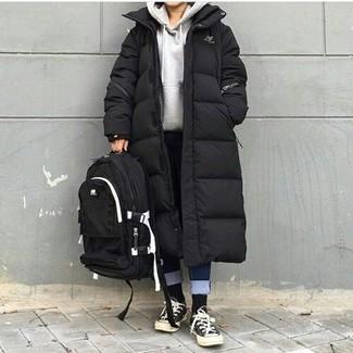Wie kombinieren: schwarzer Daunenmantel, grauer Pullover mit einer Kapuze, dunkelblaue Jeans, schwarze und weiße Segeltuch niedrige Sneakers