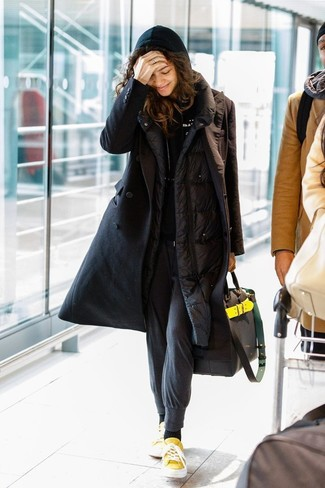 Wie kombinieren: schwarzer Daunenmantel, schwarzer Pullover mit einer Kapuze, dunkelgraue Jogginghose, gelbe Segeltuch niedrige Sneakers