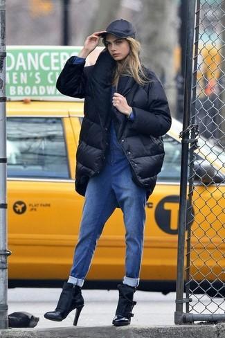 Wie kombinieren: schwarzer Daunenmantel, blauer Jumpsuit aus Jeans, schwarze Leder Stiefeletten, schwarze Baseballkappe