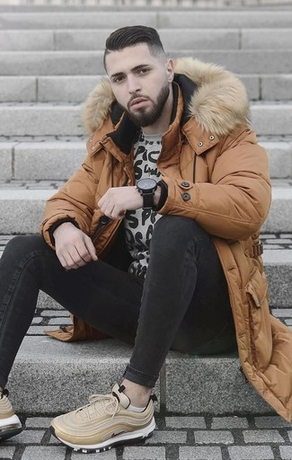 Wie kombinieren: rotbrauner Daunenmantel, graues bedrucktes Sweatshirt, schwarze enge Jeans, hellbeige Sportschuhe