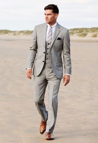 Wie kombinieren: grauer Dreiteiler, weißes Businesshemd, braune Leder Brogues, graue vertikal gestreifte Krawatte