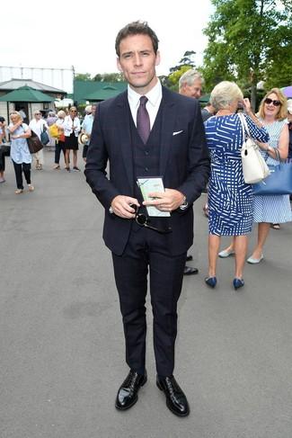 Wie kombinieren: dunkelblauer Dreiteiler mit Karomuster, weißes Businesshemd, schwarze Leder Derby Schuhe, dunkellila bedruckte Krawatte