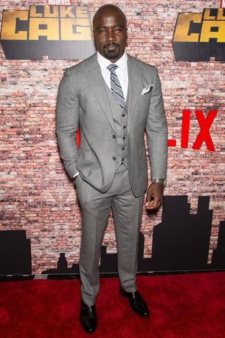 Wie kombinieren: grauer Wolldreiteiler, weißes Businesshemd, schwarze Doppelmonks aus Leder, graue vertikal gestreifte Krawatte