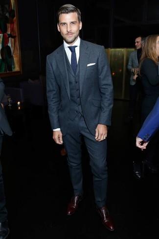 Wie kombinieren: dunkelgrauer Wolldreiteiler, weißes Businesshemd, dunkelbraune Leder Oxford Schuhe, dunkelblaue Strick Krawatte
