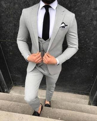 Schwarze Strick Krawatte kombinieren: trends 2020: Entscheiden Sie sich für einen klassischen Stil in einem grauen Dreiteiler und einer schwarzen Strick Krawatte. Fühlen Sie sich ideenreich? Entscheiden Sie sich für schwarze Leder Slipper mit Quasten.