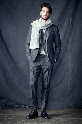 Wie kombinieren: grauer Wolldreiteiler, grauer Pullover mit einem Rundhalsausschnitt, schwarze Lederfreizeitstiefel, grauer Strick Schal