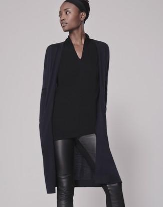 Wie kombinieren: dunkelblaue Strickjacke mit einer offenen Front, schwarze Langarmbluse, schwarze enge Hose aus Leder