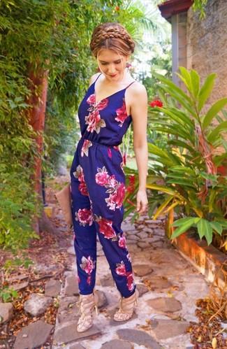 Damen Outfits 2020: Um einen unkompliziertfen und entspannten Trend-Look zu schaffen, tragen Sie einen dunkelblauen Jumpsuit mit Blumenmuster. Hellbeige Leder Sandaletten sind eine ideale Wahl, um dieses Outfit zu vervollständigen.