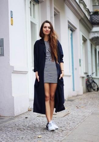 Wie kombinieren: dunkelblauer Staubmantel, weißes und dunkelblaues horizontal gestreiftes Freizeitkleid, weiße Sportschuhe