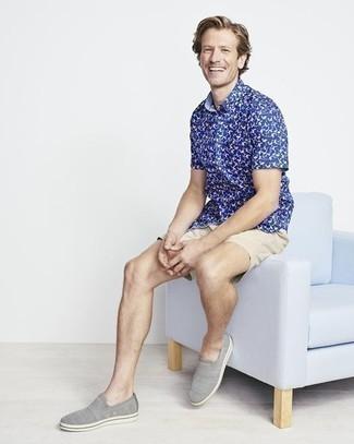 Herren Outfits 2021: Kombinieren Sie ein dunkelblaues bedrucktes Kurzarmhemd mit hellbeige Shorts für einen bequemen Alltags-Look. Graue Slip-On Sneakers aus Segeltuch sind eine großartige Wahl, um dieses Outfit zu vervollständigen.