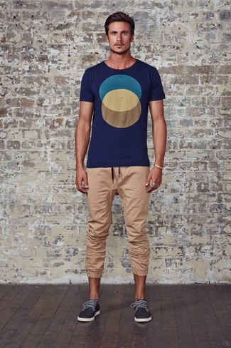 Wie kombinieren: dunkelblaues bedrucktes T-Shirt mit einem Rundhalsausschnitt, beige Jogginghose, dunkelgraue niedrige Sneakers