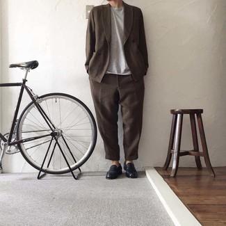 Herren Outfits 2021: Kombinieren Sie einen dunkelbraunen Anzug mit einem grauen T-Shirt mit einem Rundhalsausschnitt, wenn Sie einen gepflegten und stylischen Look wollen. Komplettieren Sie Ihr Outfit mit dunkelblauen Leder Slippern, um Ihr Modebewusstsein zu zeigen.