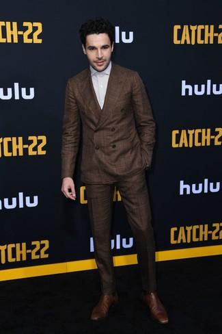 Christopher Abbott trägt dunkelbrauner Anzug, weißes vertikal gestreiftes Businesshemd, braune Chelsea-Stiefel aus Leder
