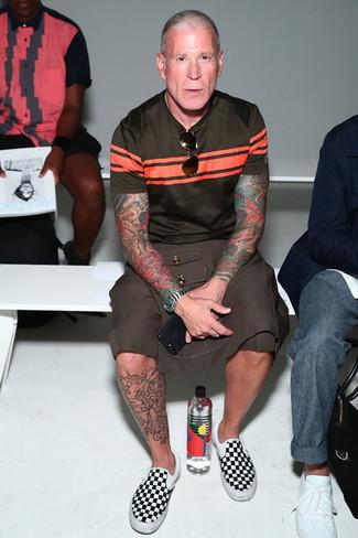 Nick Wooster trägt dunkelbraunes horizontal gestreiftes T-Shirt mit einem Rundhalsausschnitt, braune Shorts, schwarze und weiße Slip-On Sneakers aus Segeltuch mit Karomuster