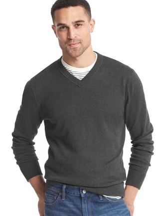 Wie kombinieren: dunkelgrauer Pullover mit einem V-Ausschnitt, weißes und schwarzes horizontal gestreiftes T-Shirt mit einem Rundhalsausschnitt, blaue Jeans
