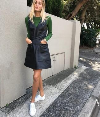 Wie kombinieren: dunkelgrüner Pullover mit einem Rundhalsausschnitt, schwarzer Leder Kleiderrock, weiße Leder niedrige Sneakers