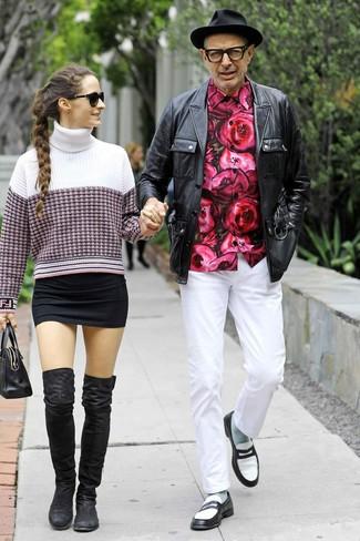 Jeff Goldblum trägt schwarze Feldjacke aus Leder, fuchsia Langarmhemd mit Blumenmuster, weiße Chinohose, schwarze und weiße Leder Slipper