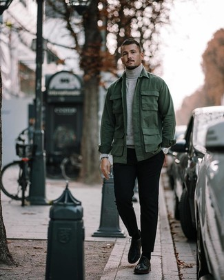 Wie kombinieren: dunkelgrüne Feldjacke, grauer Rollkragenpullover, schwarze Chinohose, schwarze Leder Derby Schuhe