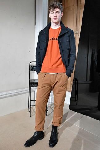 Wie kombinieren: schwarze Feldjacke, orange bedrucktes Sweatshirt, weißes T-Shirt mit einem Rundhalsausschnitt, beige Chinohose