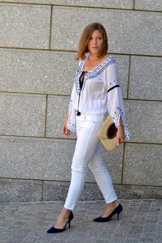 Wie kombinieren: weiße und blaue bestickte Folklore Bluse, weiße enge Jeans, schwarze Wildleder Pumps, hellbeige Stroh Clutch