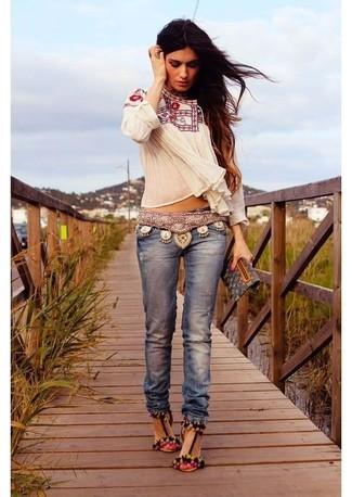 Wie kombinieren: weiße bestickte Folklore Bluse, blaue Jeans, mehrfarbige Wildleder Sandaletten, schwarze bedruckte Leder Clutch